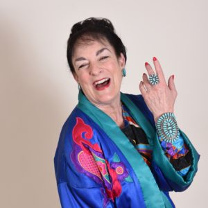 Picture of Nancy Wyatt, My Get Well Guru, in coat of many colors showing turquoise ring and bracelet created by Native Americans