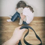 Little girl crying in corner; hand with strap in front