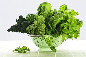 Dark green leafy fresh vegetables in light green colander
