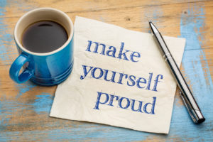 """The words, """"Make yourself proud"""" - handwriting on a napkin with a blue cup of espresso coffee"""