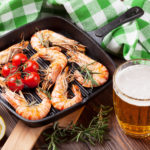 Grilled shrimps on frying pan and beer on wooden table for meal during training session