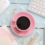 pink coffee cup plus laptop and writing utensils on a pale blue writing surface to create works for Write by the Rails