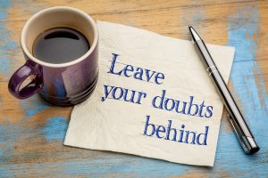 """""""Leave your doubts behind"""" - handwriting on a napkin with a purple cup of espresso coffee"""