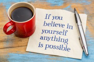 If you believe in yourself anything is possible - handwriting on a napkin with a red cup of espresso coffee