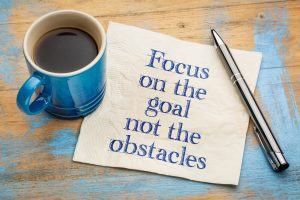 Focus on the goal, not obstacles - handwriting on a napkin with a blue cup of espresso coffee