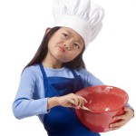 Young Girl in chef's hat stirring mixture in a red bowl for Baking