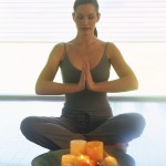 woman meditating on mat w candles - MS ClipArt